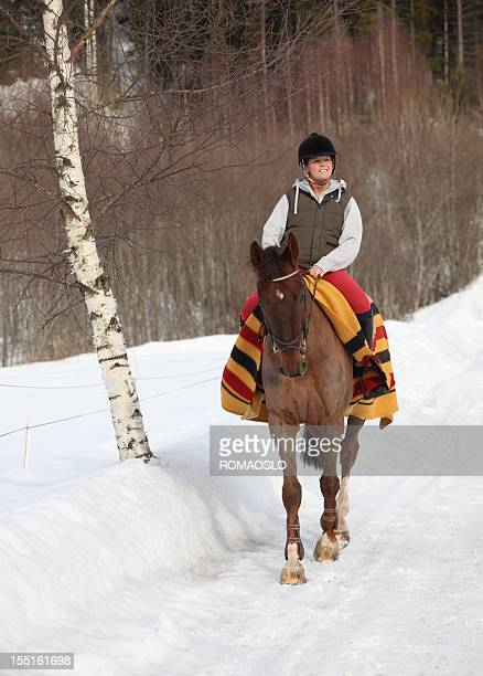 Young woman horseback riding in the snow, Oslo Norway