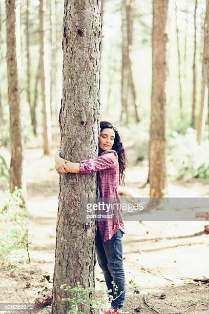 Junge Frau umarmen einen Baum im Wald