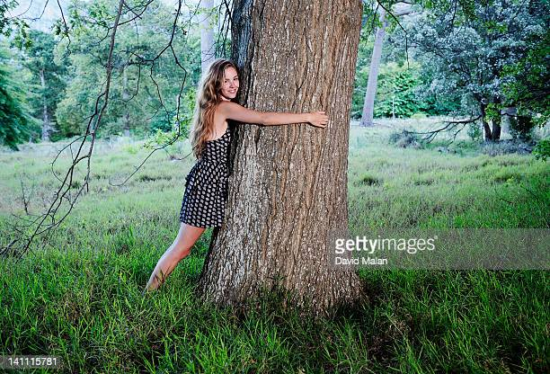 Young woman hugging a tree.