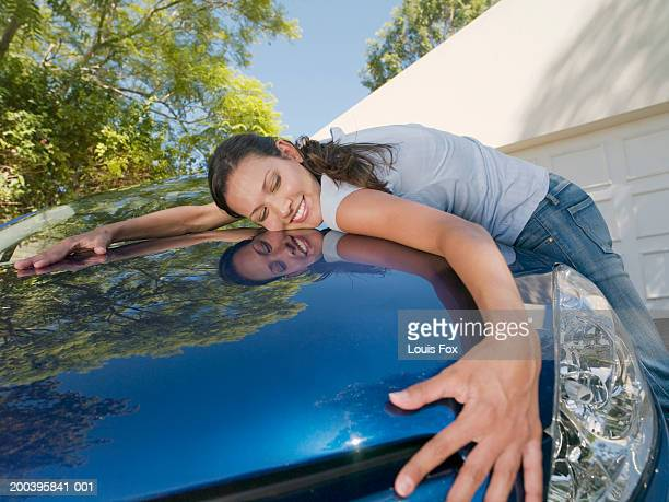 Young woman hugging car, smiling, eyes closed