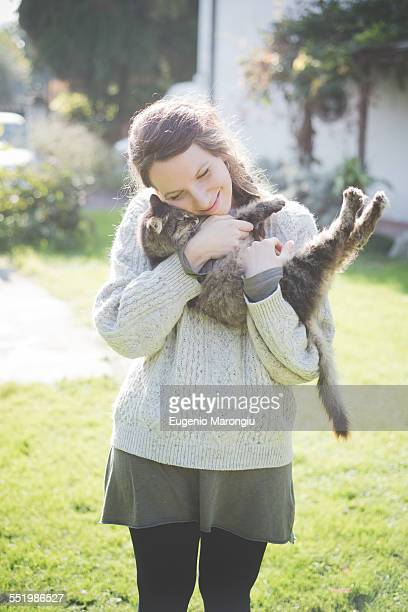 Young woman hugging cat