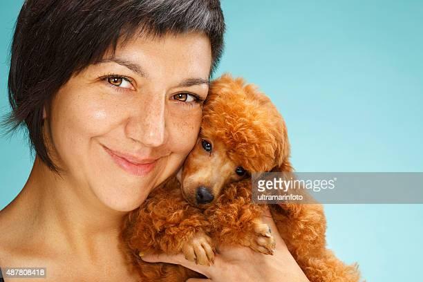 若い女性を包みこむ可愛らしいミニアチュアプードルの子犬犬のお友達