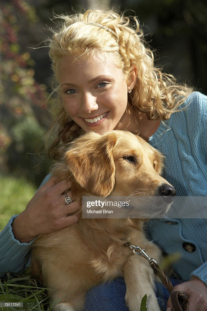 Young woman hugging dog outdoors, portrait : Stock Photo