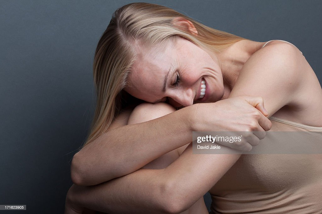 Young woman hugging herself