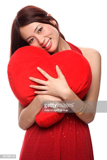 Young woman hugging red heart shaped pillow