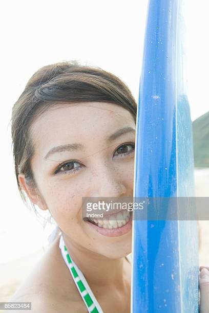 Young woman hugging surf board, smiling, portrait