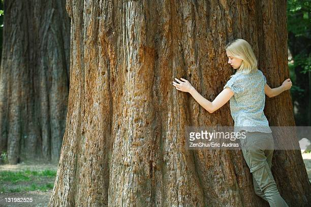 Young woman hugging tree with eyes closed