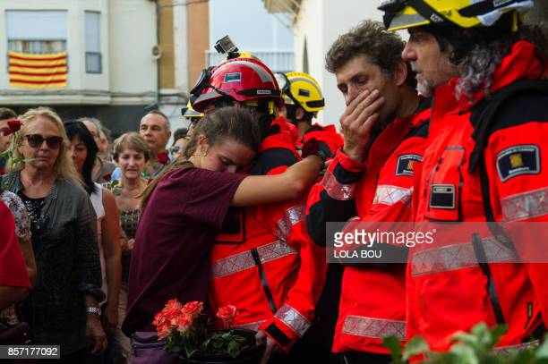 TOPSHOT A young woman hugs a fireman as others queue to lay flowers on ballot boxes used during the Catalan independence referendum in Pineda de Mar...