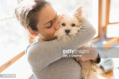 Young woman hugs Morkie breed dog