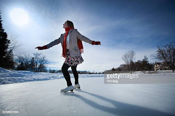 Giovane donna Ice skate all'aperto, pista di pattinaggio su ghiaccio