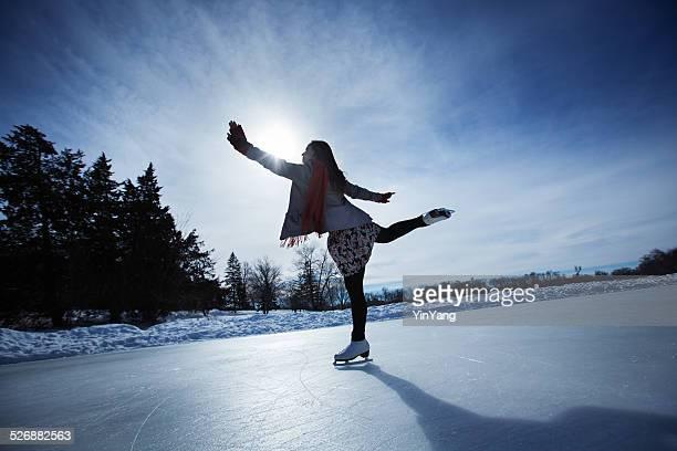 若い女性アイススケータースケーティングに冬季屋外アイスリンク