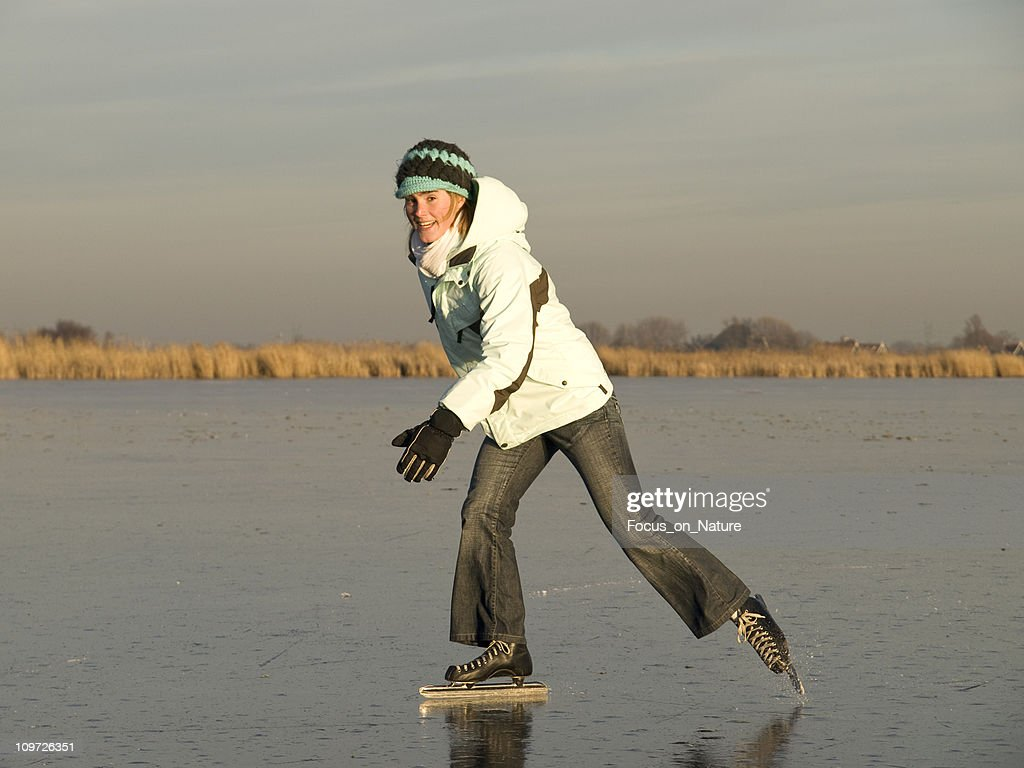 Young Woman Ice Skating on Pond in Field : Stock Photo