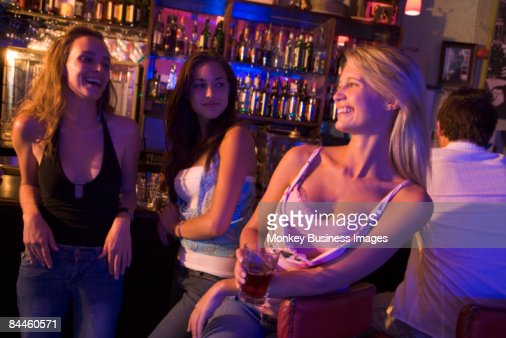 Young woman in a bar with friends : Stock Photo