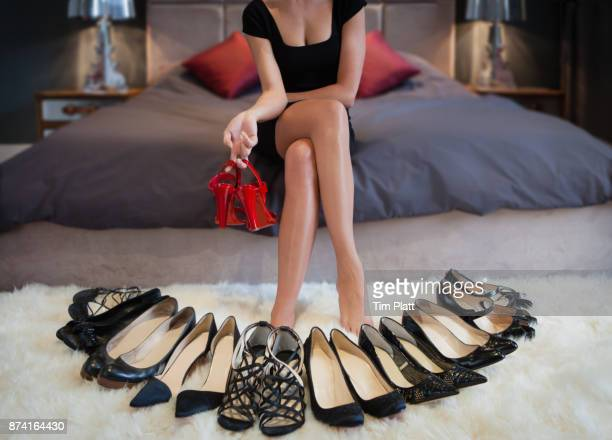 Young woman in a bedroom with a choice of shoes