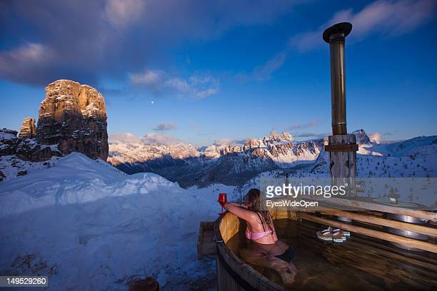 A young woman in a bikini is taking a bath and relaxing in the hot bath tub of the alpine mountain hut Rifugio Scoiattoli that faces the famous rocks...