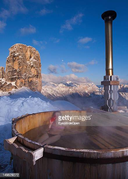 A young woman in a bikini is taking a bath in the hot bath tub of the alpine mountain hut Rifugio Scoiattoli that faces the famous rocks called...
