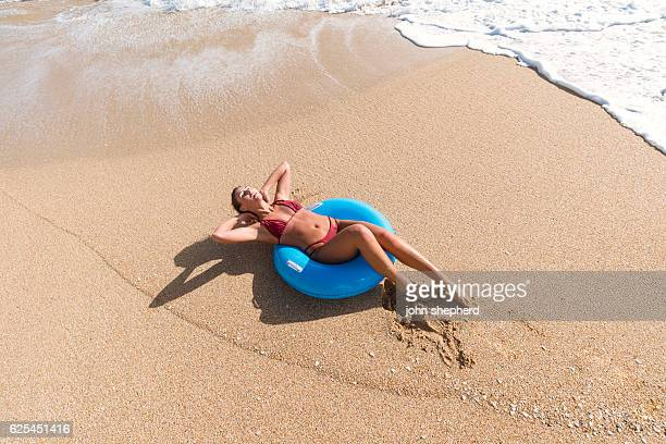 young woman in a blue rubber ring enjoying the beach