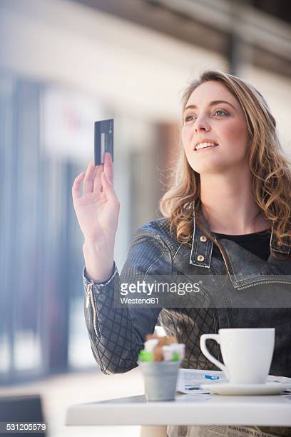Young woman in a cafe paying with credit card
