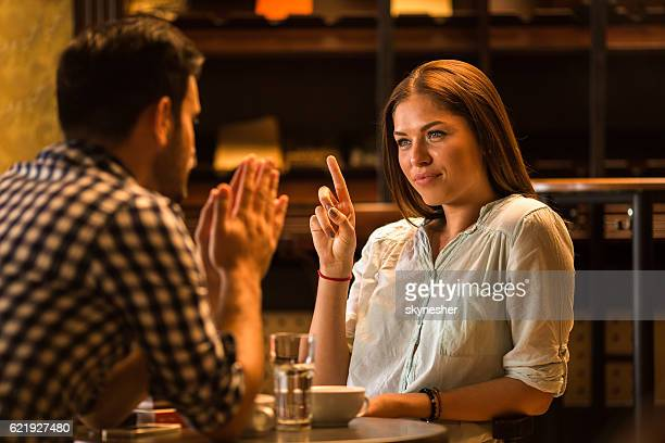 Young woman in a cafe scolding her boyfriend.