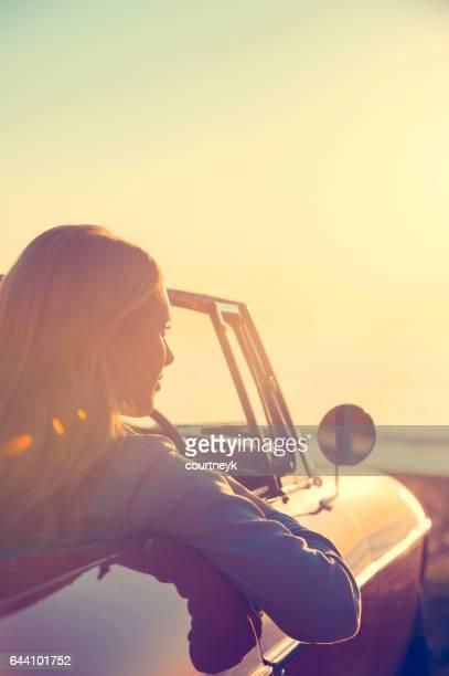 Jonge vrouw in een auto op het strand.