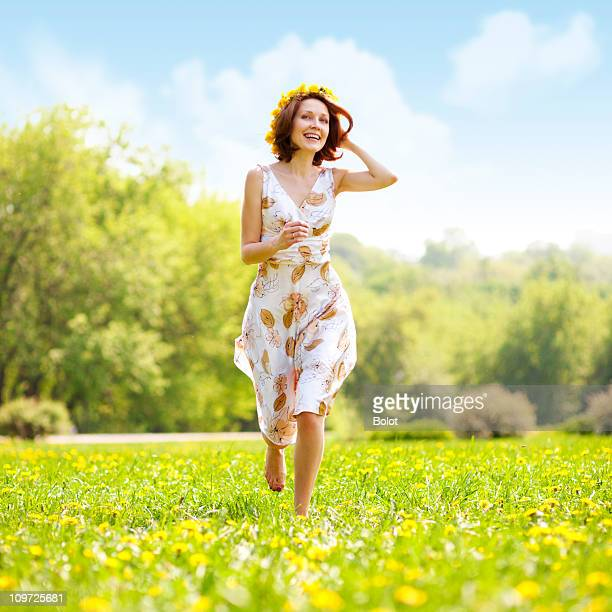 A young woman in a dress running through the grass field
