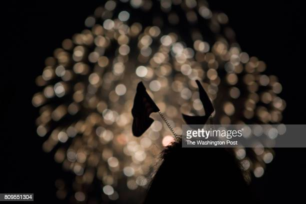 A young woman in a flag headband watches the fireworks at the Washington Monument in Washington DC on July 4 2017