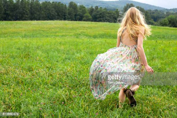 young woman in a floral dress running in a meadow