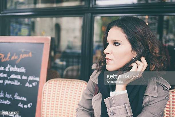 Young woman in a Parisian sidewalk cafe (Paris, France)