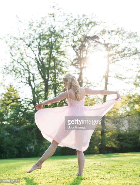 Young Woman In A Pink Dress Dancing In A Garden - Backlit