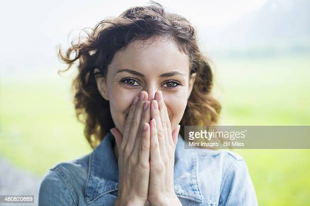 A young woman in a rural landscape, with windblown curly hair. Covering her face with her hands, and laughing.