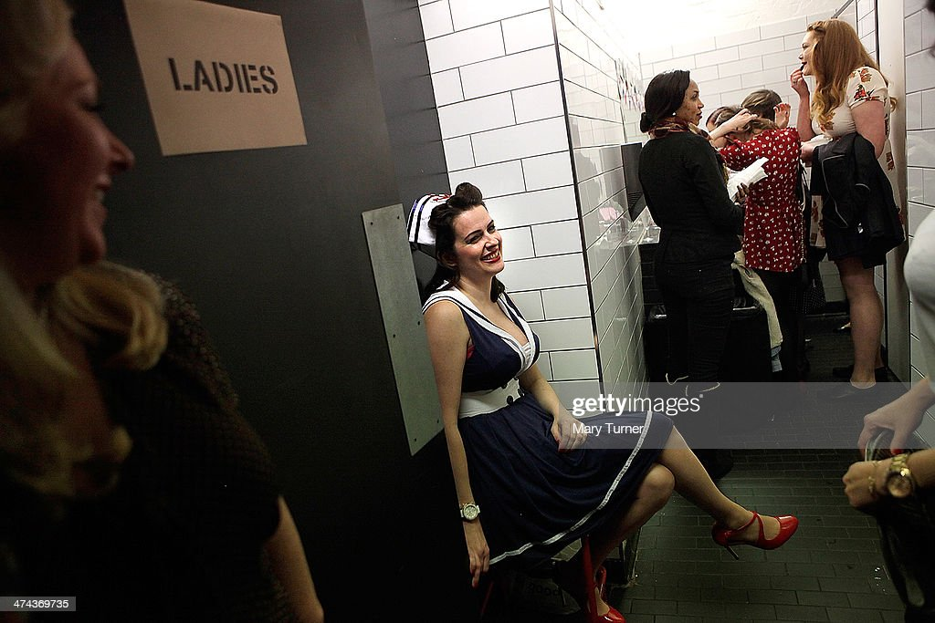 A young woman in a sailor-style uniform takes a break as she waits in the queue to check her make up at The Blitz Party on February 22, 2014 in London, England. Deep in an East End bunker hundreds of vintage enthusiasts partied like it was 1940 in a range of 1940s costumes, dancing to Swing and Jazz music while drinking wartime themed cocktails as they embraced the glamour of and nostalgia for the era.