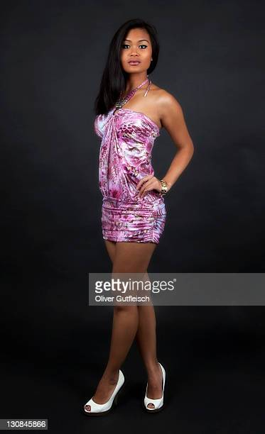 Young woman in a short dress and high heels posing, standing