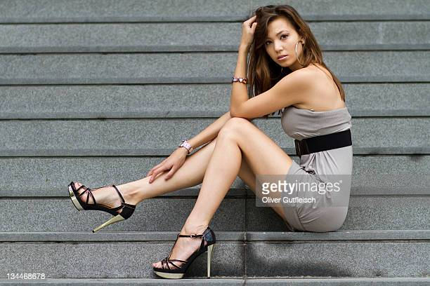 Young woman in a short gray dress and high heels sitting on stone stairs