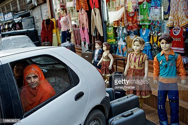 A young woman in a traditional Muslim dress sits in a car outside a store of fashionable clothes When Sharia law prevailed in Kashmir it was...