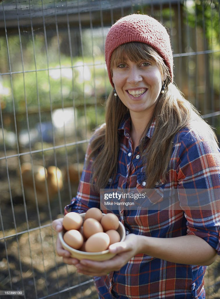 Young woman in allotment holding free range eggs : Stock Photo