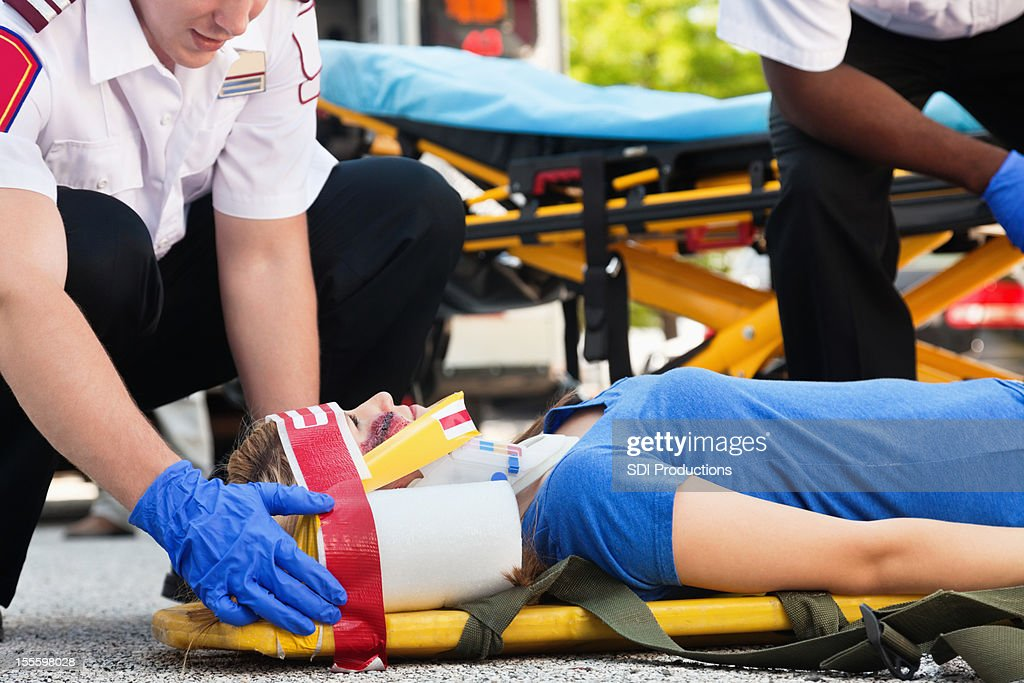 Young woman in an ambulance stretcher beinng treated by medics : Stock Photo