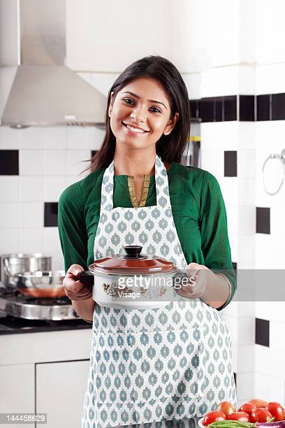 Young woman in apron holding a casserole in a kitchen, Portrait