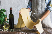 Young woman in apron holding a dough for homemade pasta at rustic kitchen