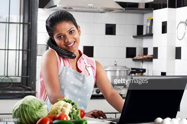Young woman in apron, speaking on phone and working with laptop in a kitchen
