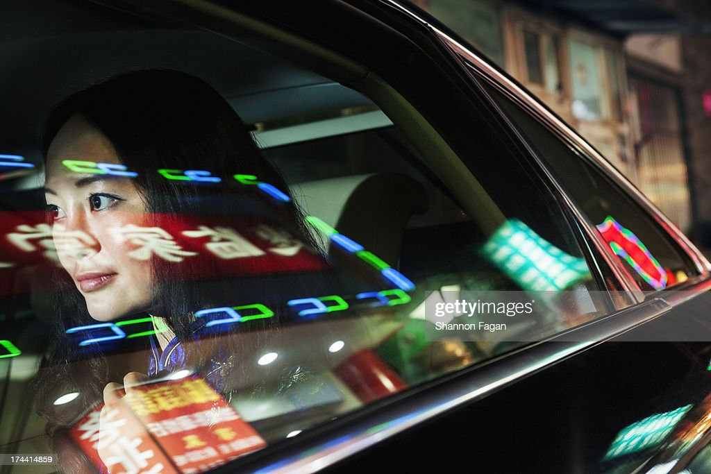 Young Woman In Backseat of Car, Reflected Lights : Stock Photo