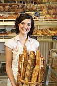 Young woman in bakery, holding basket of baguettes, smiling, portrait