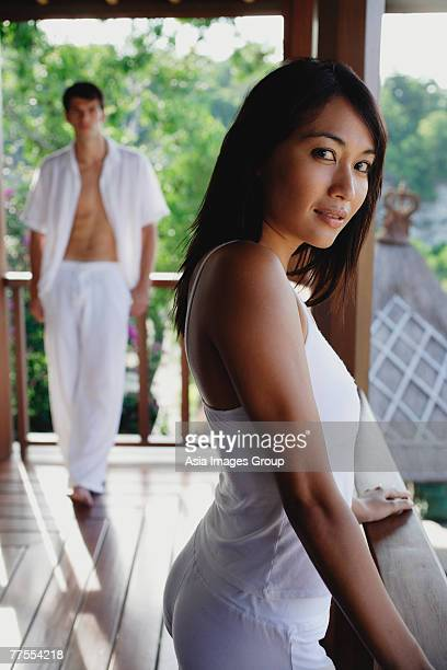 Young woman in balcony looking at camera, man standing in background