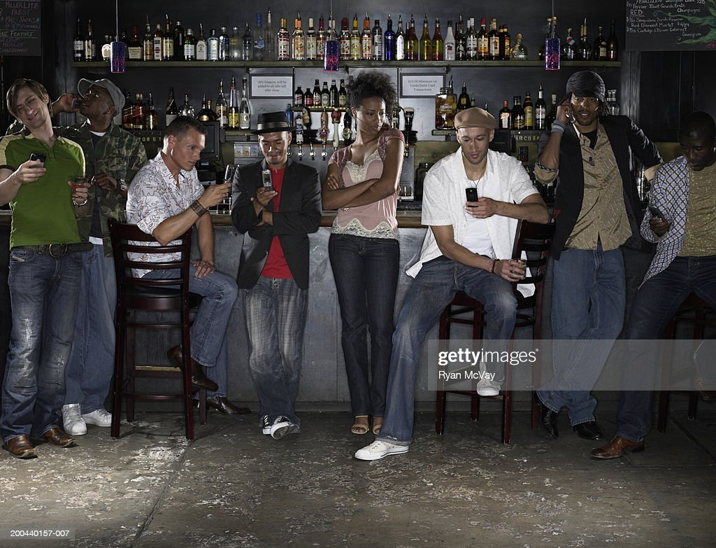 Young woman in bar watching group of men using cell phones : Stock Photo