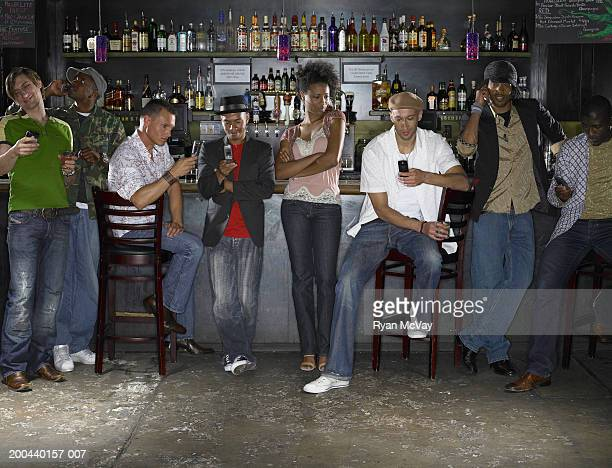 Young woman in bar watching group of men using cell phones