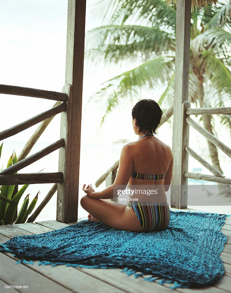 Young woman in bathing suit meditating on porch of  beach hut : Stock Photo