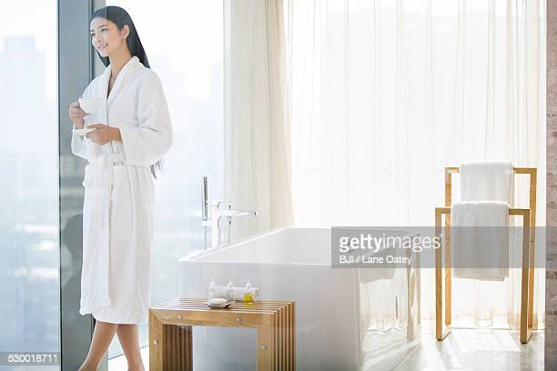 Young woman in bathrobe drinking coffee