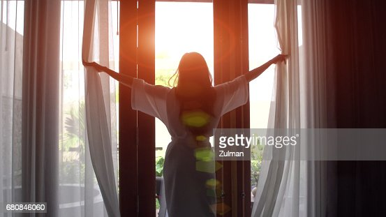 Young woman in bathrobe open curtains and stretch standing near the window at home. : Stock Photo