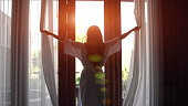 Young woman in bathrobe open curtains and stretch standing near the window at home. 4K
