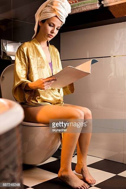 Young woman in bathrobe reading magazine in toilet.