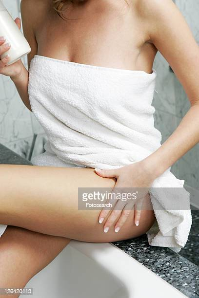 Young woman in bathroom, applying body lotion
